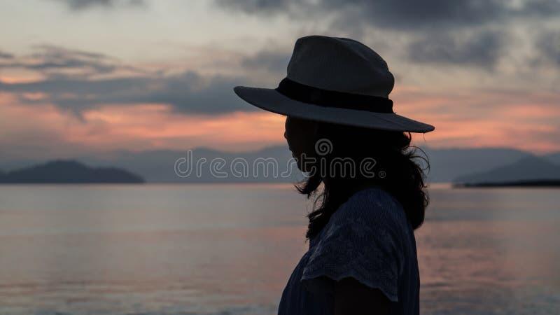 Aziatisch vrouwensilhouet bij zonsopgang oceaan roze en oranje hemel stock afbeeldingen