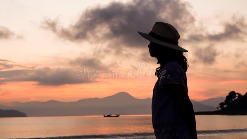 Aziatisch vrouwensilhouet bij zonsopgang oceaan roze en oranje hemel royalty-vrije stock foto's