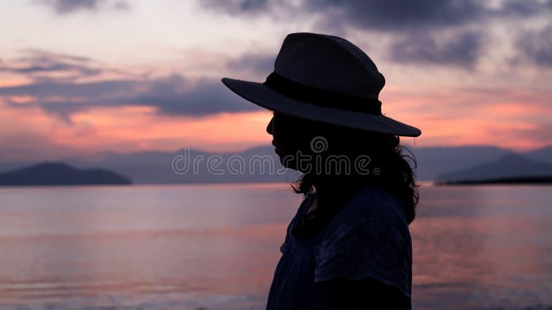 Aziatisch vrouwensilhouet bij zonsopgang oceaan roze en oranje hemel royalty-vrije stock foto