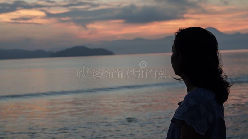 Aziatisch vrouwensilhouet bij zonsopgang oceaan roze en oranje hemel stock fotografie