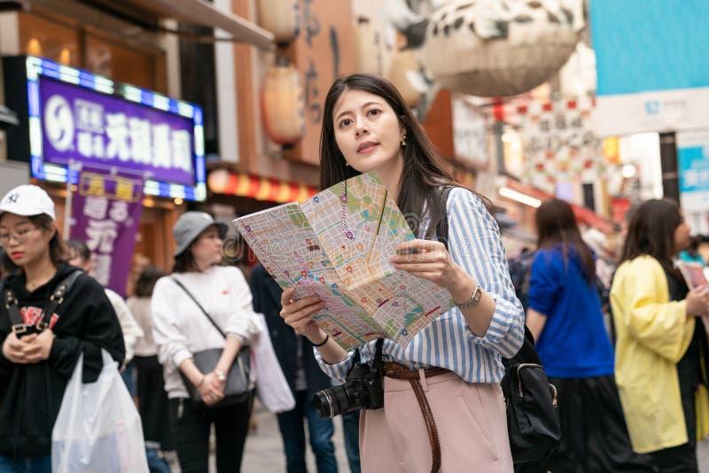 Aziatisch wijfje die haar doel op de kaart proberen te vinden royalty-vrije stock afbeelding