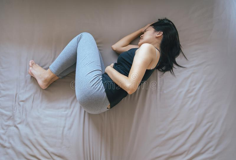 Aziatisch wijfje die pijnlijke maagpijn, Vrouw hebben die aan buikpijn, Periodeklemmen lijden royalty-vrije stock afbeelding