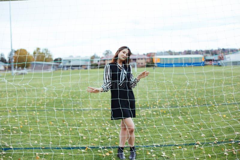 Aziatisch wijfje die in voetbalspeelplaats het net houden stock afbeelding