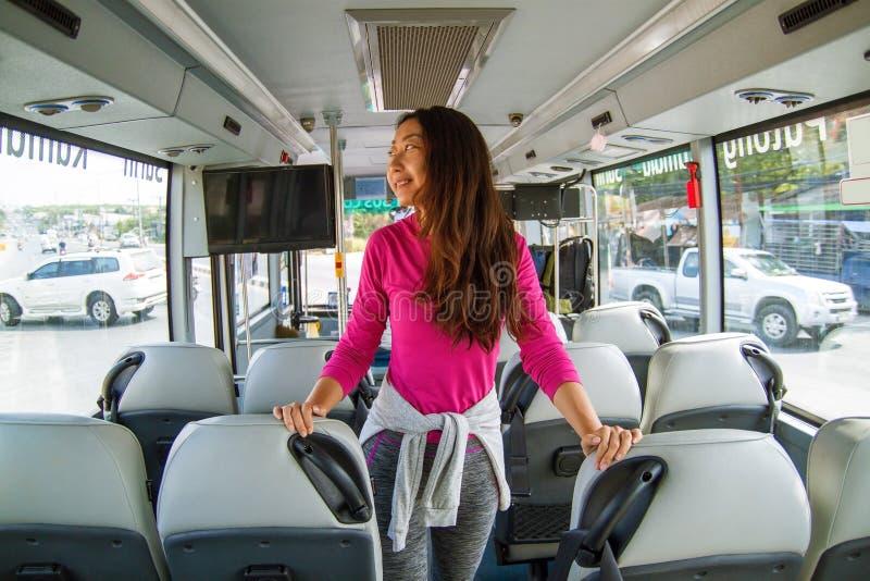 Aziatische aantrekkelijke vrouwenreiziger met lang haar die zich in bus bevinden en van de reis genieten stock afbeeldingen