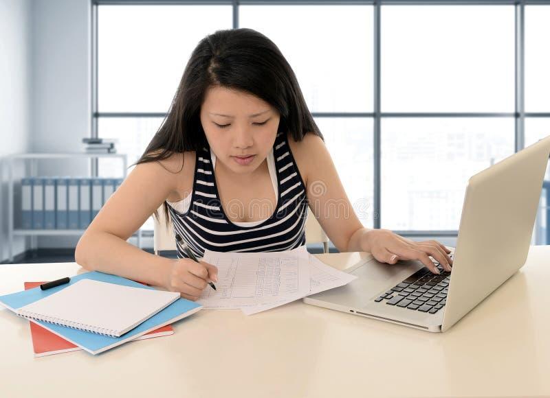 Aziatische Amerikaanse student die met een glimlach op modern bibliotheekkantoor werken en voor examen met computerlaptop bestude royalty-vrije stock afbeelding