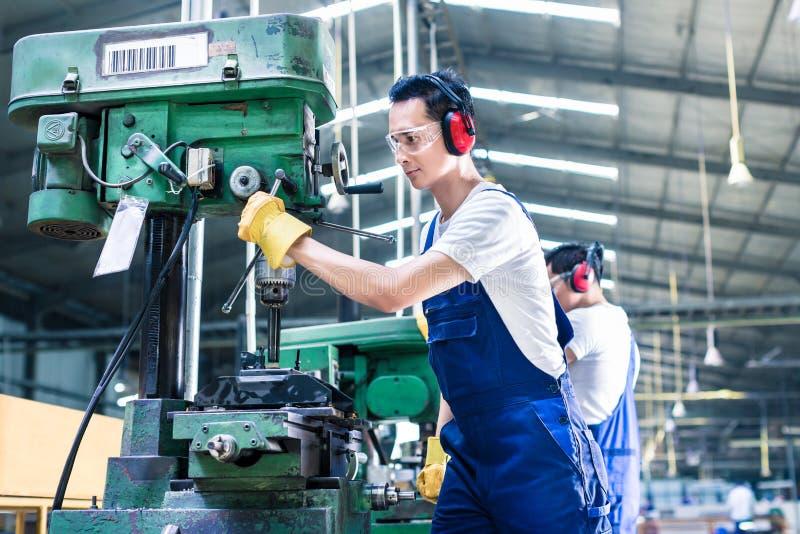 Aziatische arbeider in de boring van de productiefabriek royalty-vrije stock fotografie