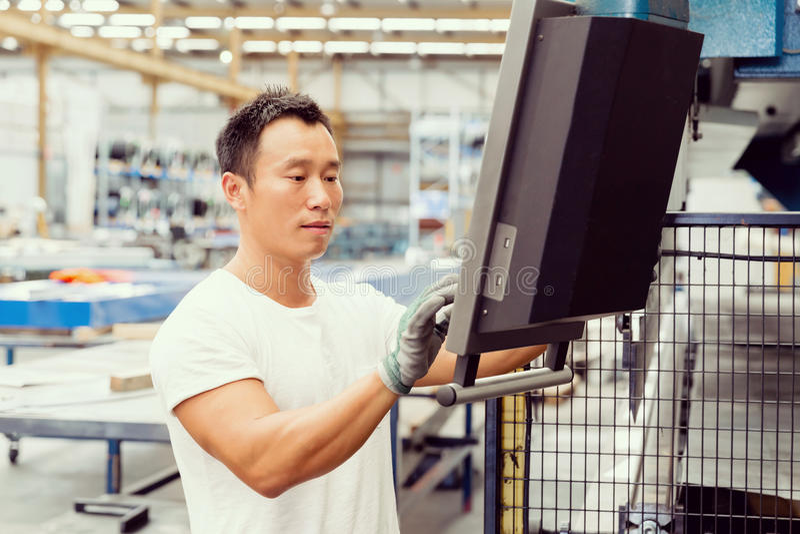 Aziatische arbeider in productie-installatie op de fabriek stock foto