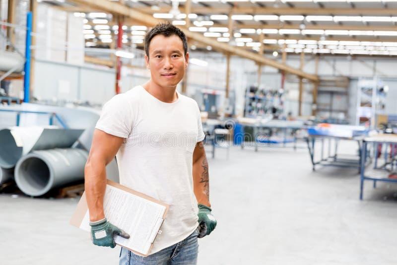 Aziatische arbeider in productie-installatie op de fabriek stock fotografie