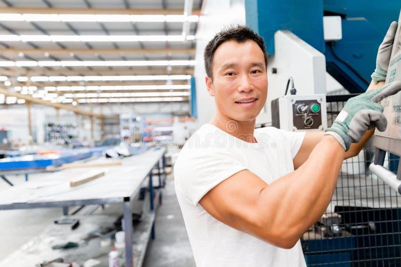 Aziatische arbeider in productie-installatie op de fabriek royalty-vrije stock afbeelding