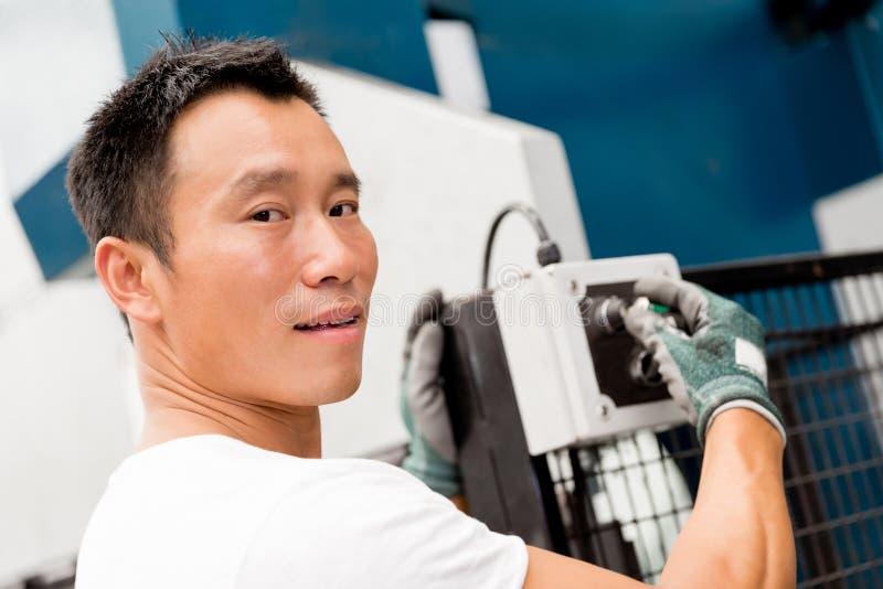 Aziatische arbeider in productie-installatie op de fabrieksvloer stock afbeelding