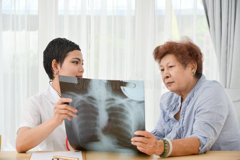 Aziatische arts en hogere patiënt die xray film samen bekijken stock afbeeldingen