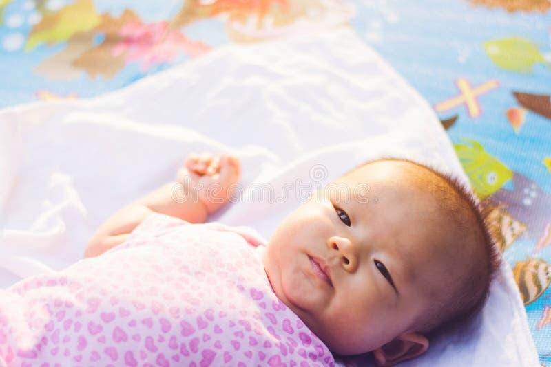 Aziatische baby die op grond bij park bepalen royalty-vrije stock afbeeldingen