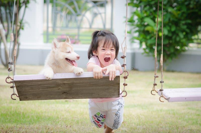 Aziatische babybaby op schommeling met puppy stock afbeeldingen