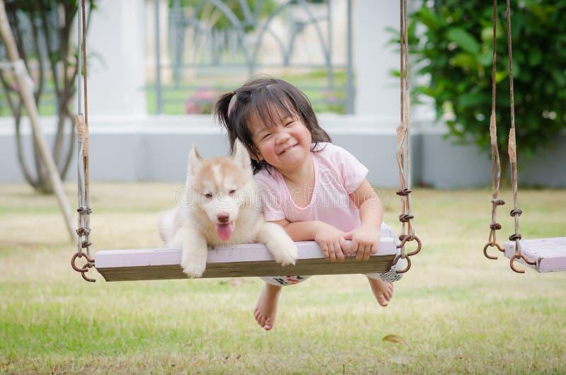 Aziatische babybaby op schommeling met puppy royalty-vrije stock afbeeldingen