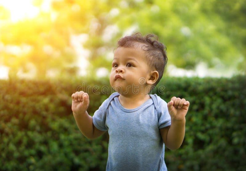 Aziatische Babyjongen die zich in groene aard bevinden stock afbeelding