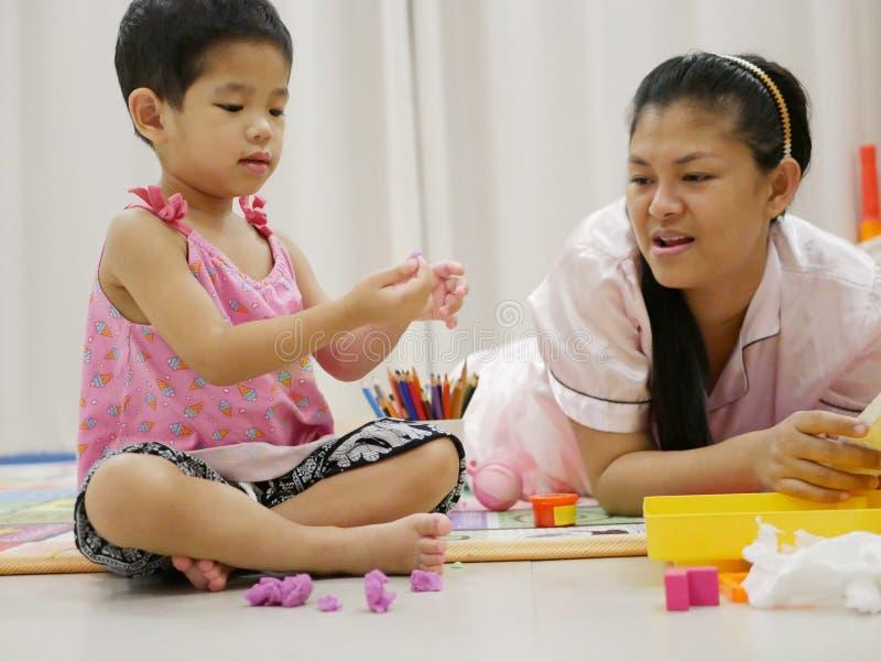 Aziatische babymeisje het spelen plasticine met haar moeder thuis stock foto's