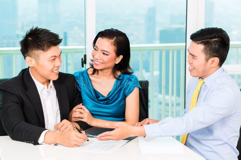 Aziatische bankiers verkopende verzekering aan paar royalty-vrije stock afbeelding