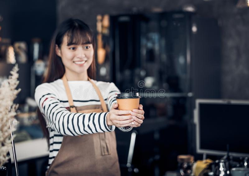 Aziatische Barista diende omhoog koffie met glimlach bij de mok van de koffieholding met hand twee met het glimlachen gezicht bij stock fotografie