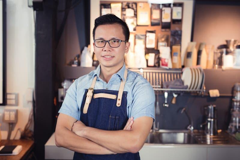 Aziatische barista status die in koffiewinkel glimlachen, Aziatische knap me royalty-vrije stock afbeelding