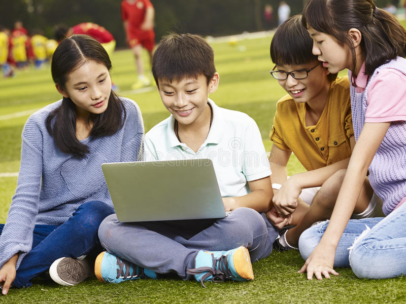Aziatische basisschoolkinderen die laptop in openlucht met behulp van royalty-vrije stock afbeeldingen
