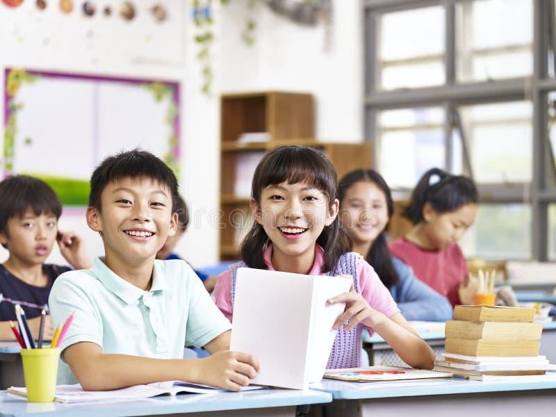 Aziatische basisschoolstudenten in klaslokaal royalty-vrije stock afbeeldingen