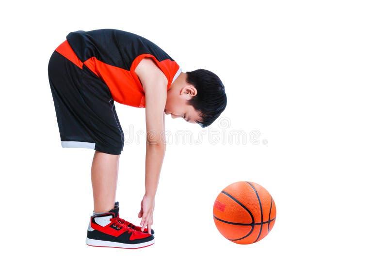 Aziatische basketbalspeler die onderaan zich het uitrekken buigen Geïsoleerd op whi stock foto