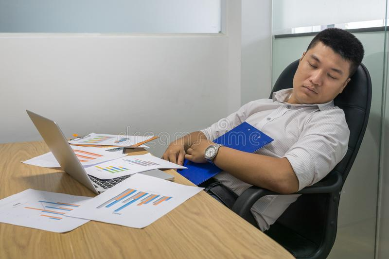 Aziatische bedrijfsleiderslaap in het bureau stock foto's
