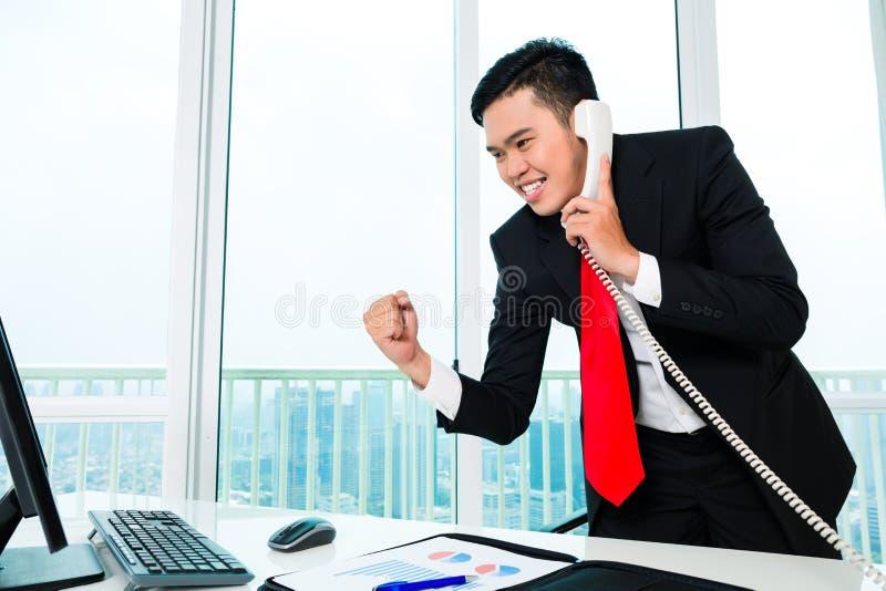 Aziatische bedrijfsmens die in bureau telefoneren stock afbeeldingen
