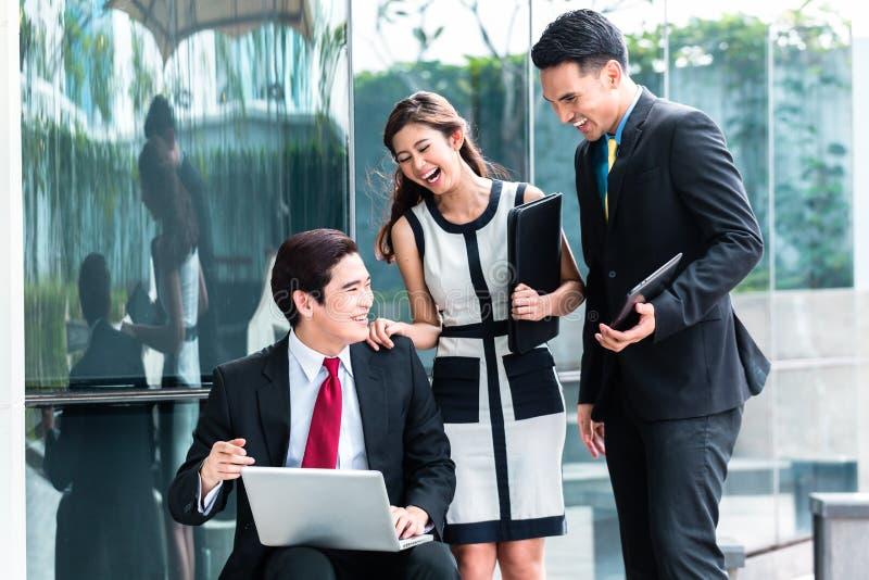 Aziatische bedrijfsmensen die buiten aan laptop werken stock afbeelding
