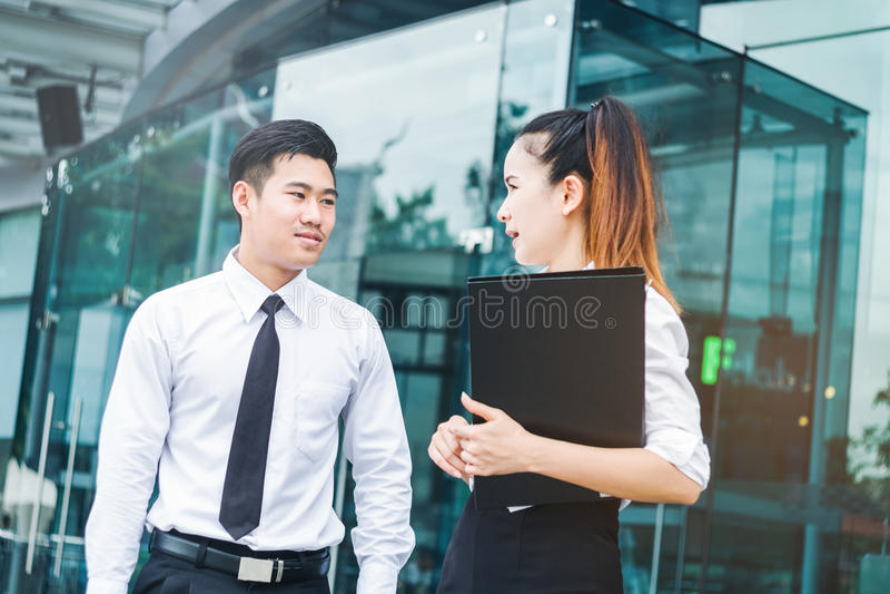Aziatische Bedrijfsmensen die buiten bureau na het werk spreken royalty-vrije stock afbeeldingen