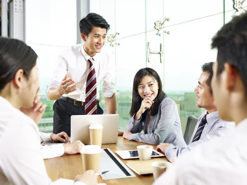 Aziatische bedrijfsmensen die in bureau samenkomen stock foto