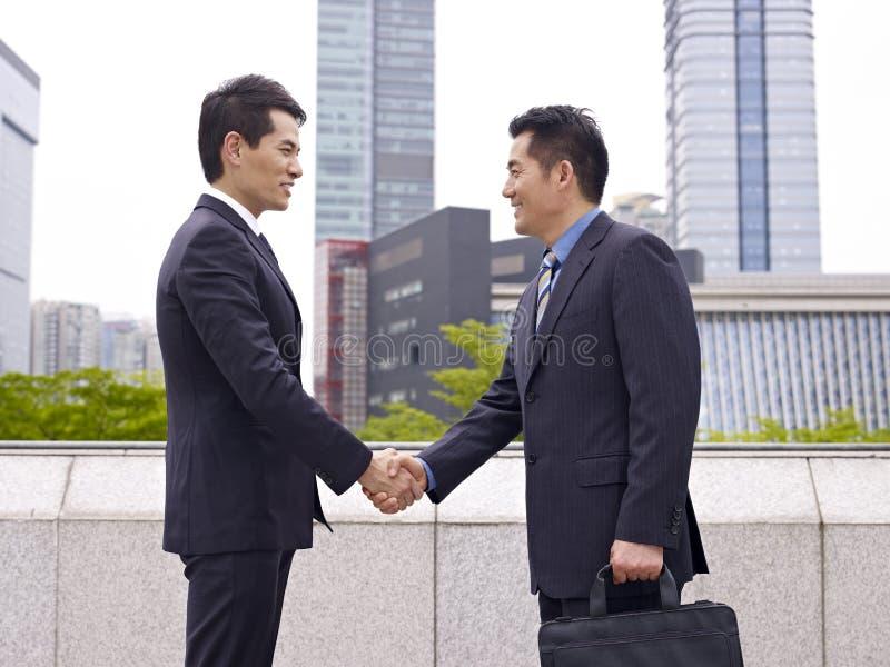 Aziatische bedrijfsmensen die handen schudden stock foto