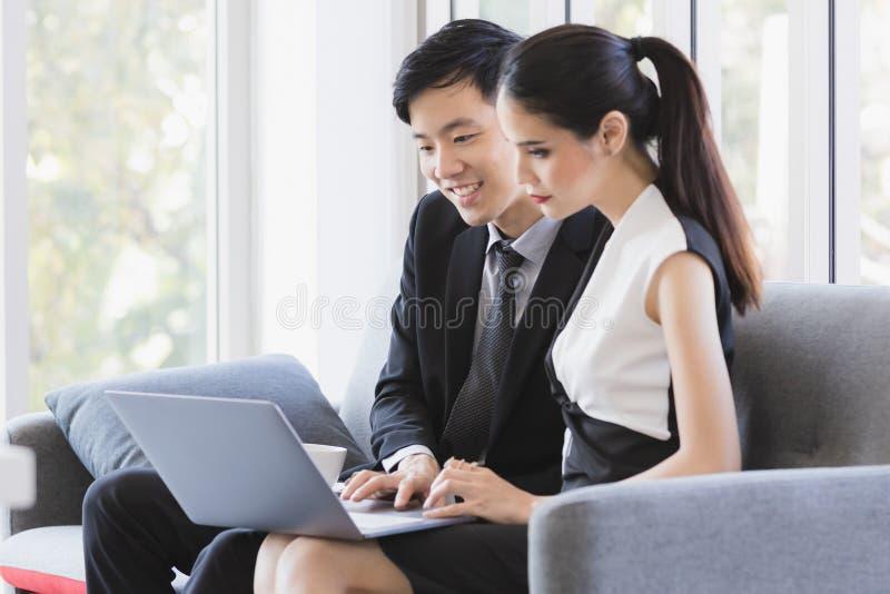 Aziatische bedrijfsmensen die laptop in bureau met behulp van stock foto