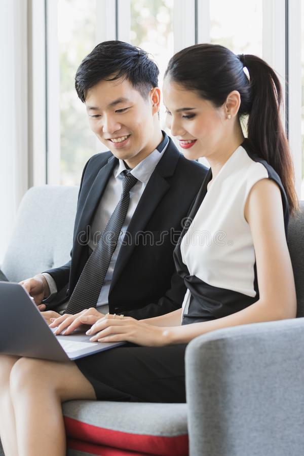 Aziatische bedrijfsmensen die laptop in bureau met behulp van stock afbeeldingen