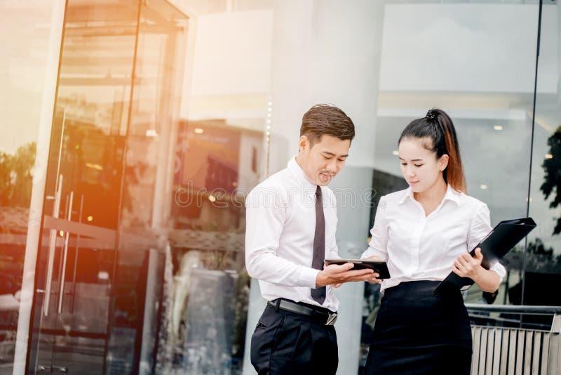 Aziatische Bedrijfspaarvergadering die digitale tablet gebruiken daarna openlucht royalty-vrije stock afbeeldingen