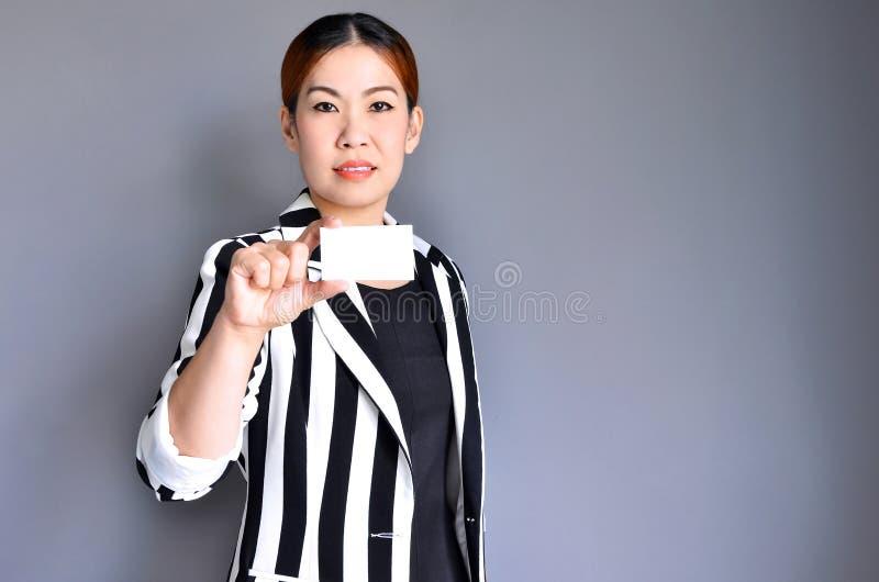 Aziatische bedrijfsvrouw die adreskaartje toont stock foto