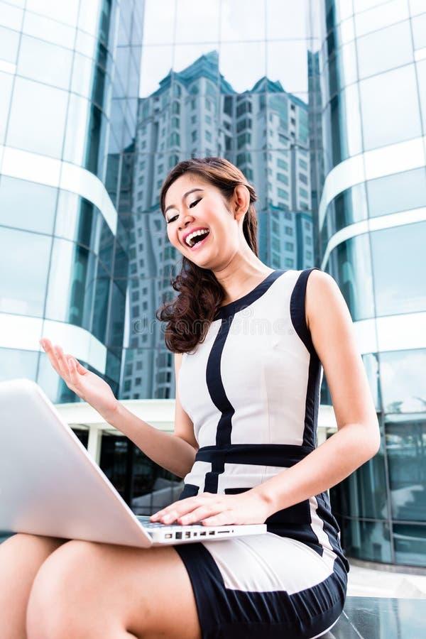 Aziatische bedrijfsvrouw die buiten aan computer werken royalty-vrije stock foto