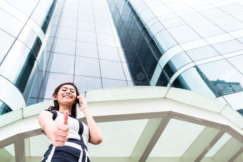 Aziatische bedrijfsvrouw die buiten met telefoon telefoneren royalty-vrije stock foto