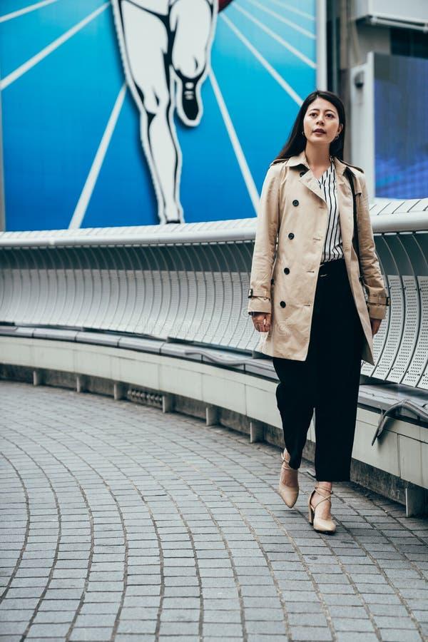 Aziatische Bedrijfsvrouw die buiten in Osaka lopen stock foto