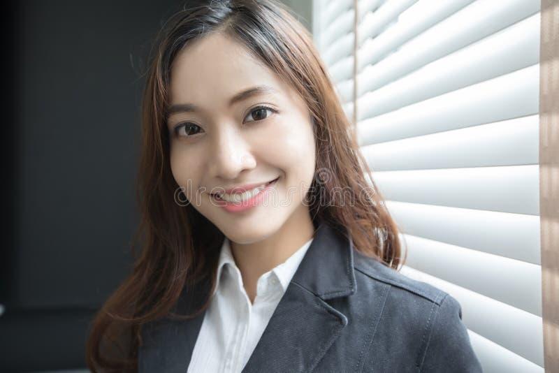 Aziatische bedrijfsvrouw die en gelukkig voor het werken in het bureau glimlachen royalty-vrije stock foto