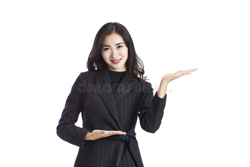 Aziatische bedrijfsvrouw die en iets tonen voorstellen royalty-vrije stock fotografie