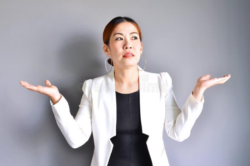 Aziatische bedrijfsvrouw die haar handen aan beide kanten op grijze bac opheffen stock afbeeldingen
