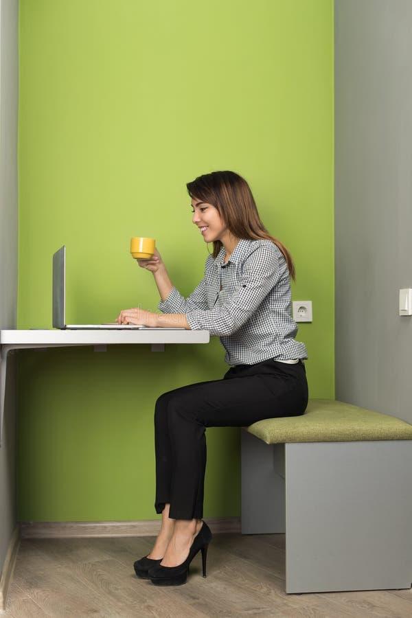 Aziatische Bedrijfsvrouw die Laptop de Kop van de de Koffiegreep van In Coworking Center van de Computeronderneemster gebruiken stock afbeelding
