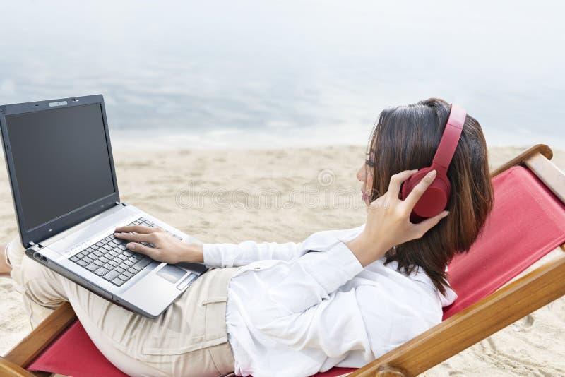 Aziatische bedrijfsvrouw die met laptop werken terwijl het gebruiken van hoofdtelefoons die in de ligstoel op strand zitten stock afbeelding