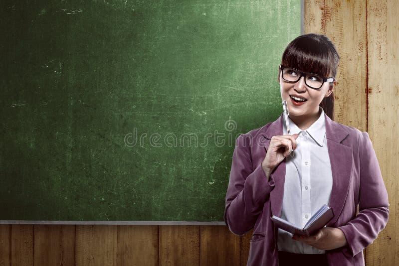 Aziatische bedrijfsvrouw die over leeg bord glimlachen stock foto