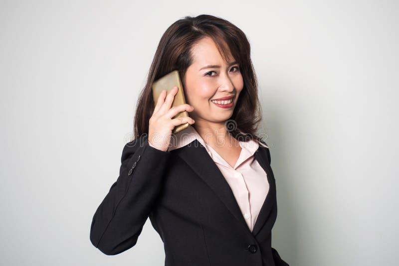 Aziatische bedrijfsvrouw die slimme telefoon met behulp van Het glimlachen en het kijken kwamen stock fotografie