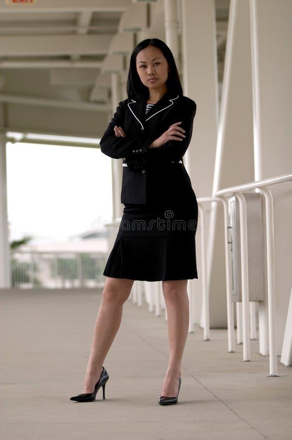 Aziatische BedrijfsVrouw die zich met Gevouwen Wapens bevindt Ernstig het Kijken stock foto