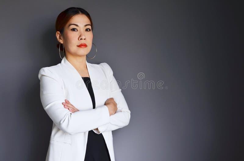 Aziatische bedrijfsvrouw die zich zeker op grijze achtergrond bevinden royalty-vrije stock fotografie