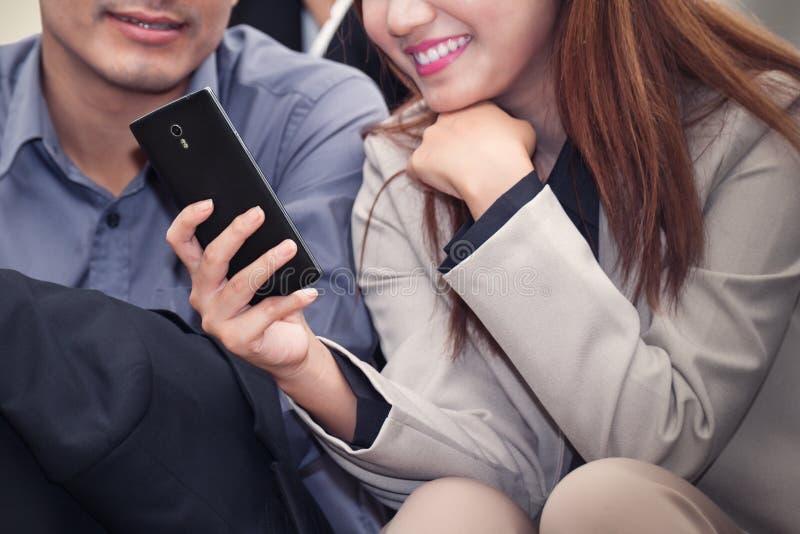 Aziatische bedrijfsvrouw en man die en celtelefoon glimlachen met behulp van togeth stock afbeelding