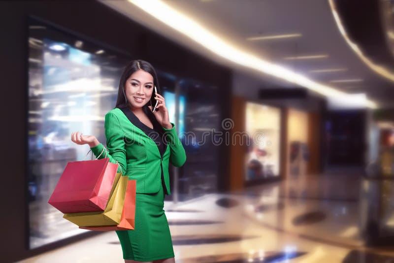 Aziatische bedrijfsvrouw met het winkelen zakken die op de telefoon spreken royalty-vrije stock foto's